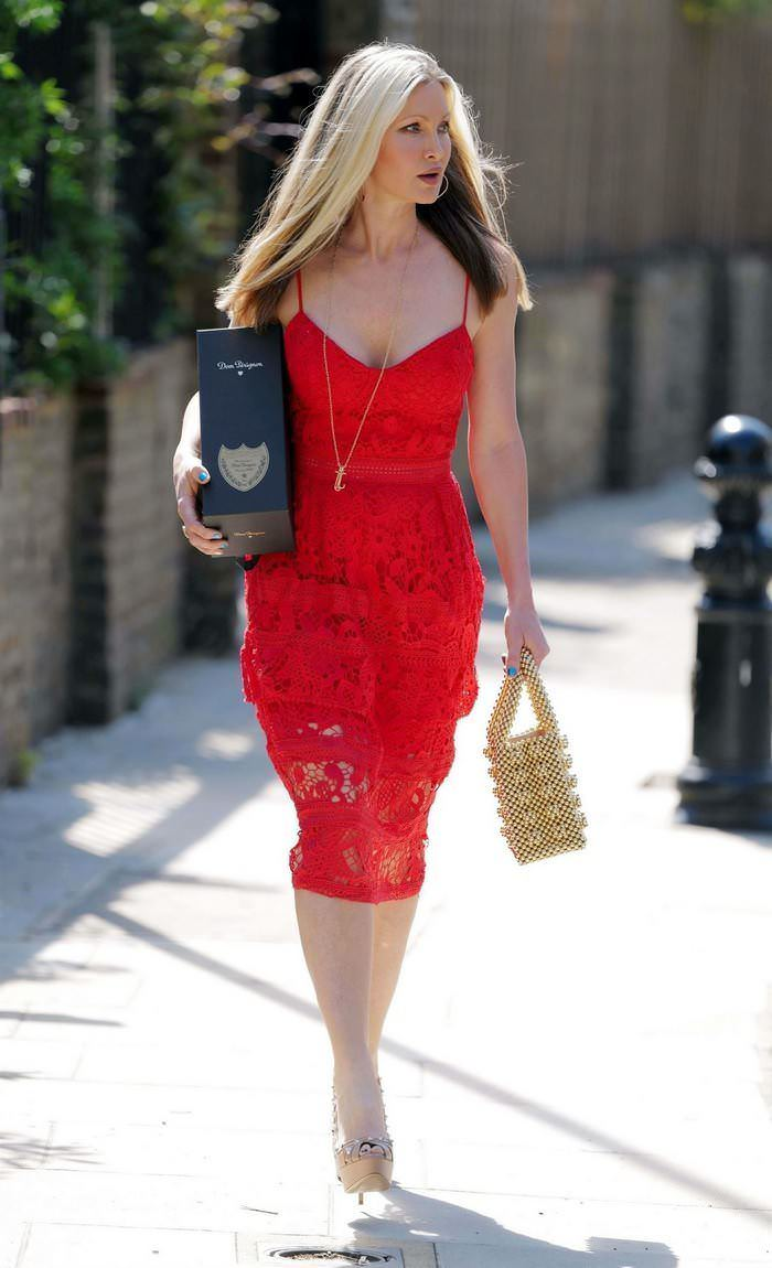 Caprice Bourret in Red Dress Carrying a Bottle of Dom Pérignon