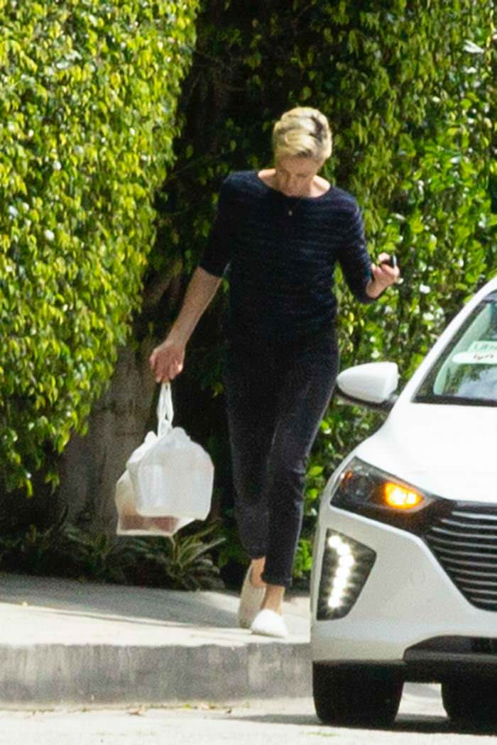 Charlize Theron Outside Her Home Grabbing a Food Delivery