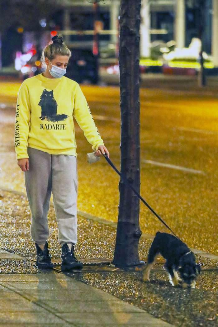 Lili Reinhart in the Yellow Sweatshirt as She Takes her Dog Out for an Evening Stroll