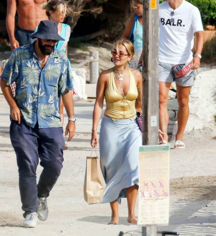 Rita Ora Opts for a Gold Crop Top as She Walks with BF in Ibiza
