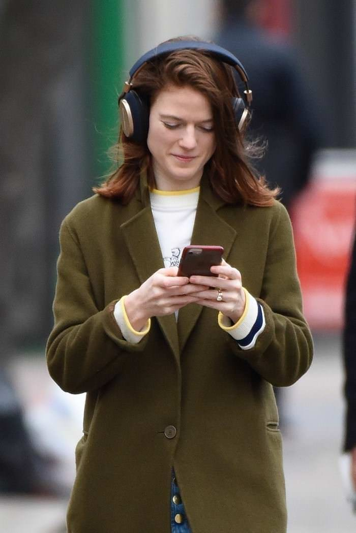 Rose Leslie Smiling While Looking at her Phone and Listening to Music in London